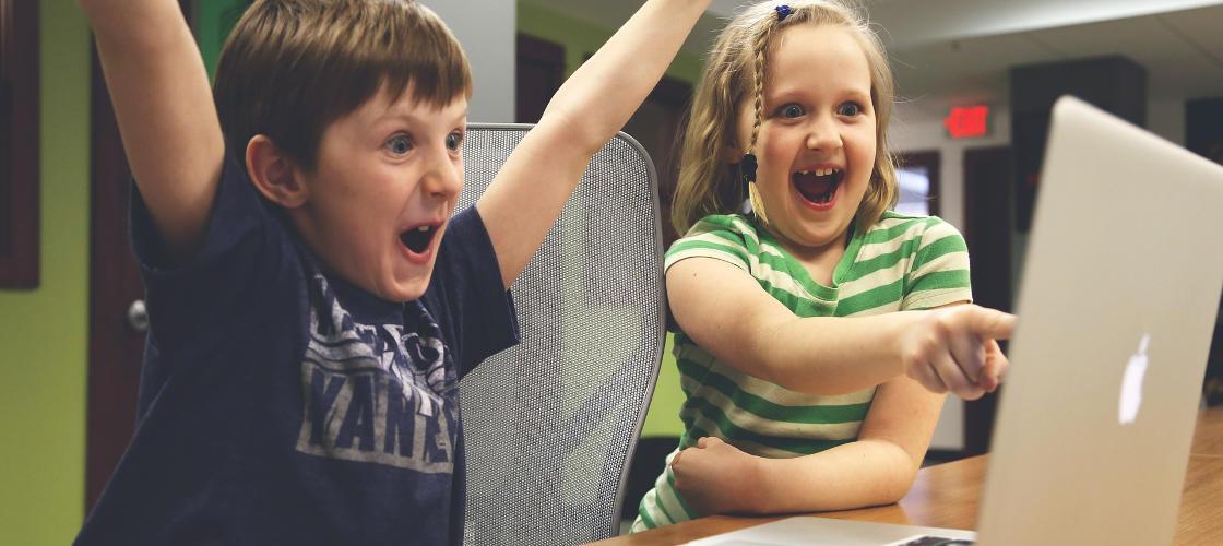 Två exalterade barn framför dator
